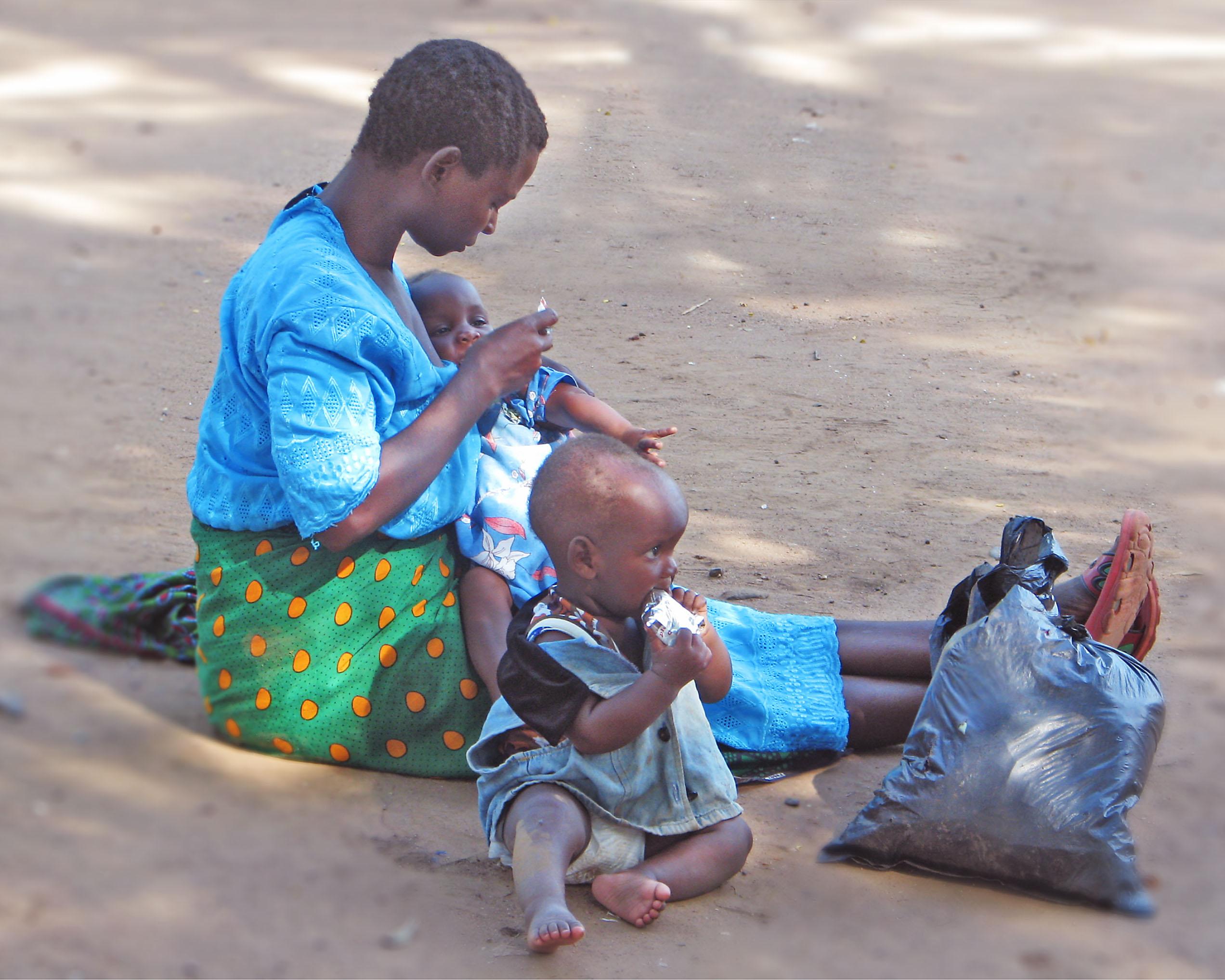 Eine Mutter in Malawi füttert ihre Zwillinge mit einer angereicherten Erdnusspaste. (Foto: Indi Trehan)